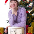Woman with clock under Christmas tree — Stock Photo