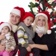 Family with two children in Santa hats — Stock Photo #35133971
