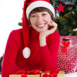 Woman in red Santa hat lying under Christmas tree with gifts — Stock Photo