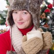 Woman in fluffy hat and mitten under Christmas tree with cup — Stok fotoğraf