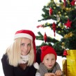 Mother and son lying under Christmas tree — Stock Photo