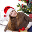 Teen girl in Santa hat with gifts under Christmas tree — Стоковая фотография