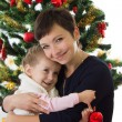 Mother hugging daughter under Christmas tree — Stock Photo