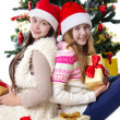 Sisters with gifts under Christmas tree — Stock Photo