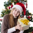 Stock Photo: Teenage girl in Santa hat with present under Christmas tree