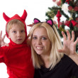 Stock Photo: Mother and son in deuce costumes under Christmas tree