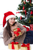 Teen girl in Santa hat with gifts under Christmas tree — Stock Photo