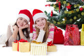 Smiling sisters in Santa hats lying under Christmas tree — Stock fotografie