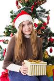 Teenage girl in Santa hat with present under Christmas tree — Foto Stock