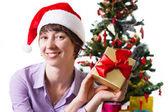 Mulher de chapéu de papai noel com presente debaixo da árvore cristmas — Fotografia Stock