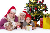 Happy family with two children in Santa hats under Christmas tree — Stok fotoğraf