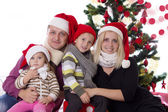 Family with two children in Santa hats — Stok fotoğraf