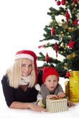 Mother and son lying under Christmas tree — Stock fotografie
