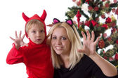 Mother and son in deuce costumes under Christmas tree — Stock Photo