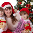 Smiling mother and two daughters under Christmas tree — Stock Photo