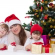 Mother and two daughters under Christmas tree — Stock Photo