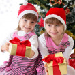 图库照片: Little sisters with gifts under Christmas tree
