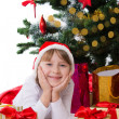 Girl in Santa hat lying under Christmas tree — Stock Photo