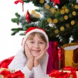 Girl in Santa hat lying under Christmas tree — Stock Photo #35238753