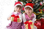 Little sisters with gifts under Christmas tree — 图库照片