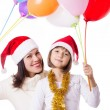 Smiling mother with daughter with balloons and Christmas hats — ストック写真