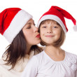Happy mother kissing daughter on cheek in Christmas hat — Stock Photo