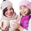 Happy mother and daughter in knitted hats with hot beverages — Стоковая фотография