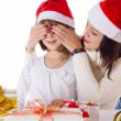Mother covering daughter eyes with hands hiding Christmas gifts — 图库照片