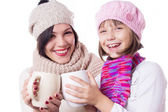 Happy mother and daughter in knitted hats with hot beverages — Стоковое фото