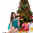 Pretty girl in fancy dress under Christmas tree — Stock Photo
