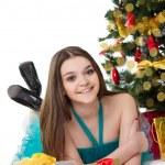 Brunette girl in fancy dress lying under Christmas tree — Stock Photo #35900197