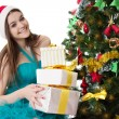 Santa helper girl with pile of presents under Christmas tree — Stock Photo