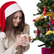 Teenage girl with coffee mug under Christmas tree — Foto de Stock