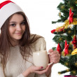Teenage girl with coffee mug under Christmas tree — Zdjęcie stockowe