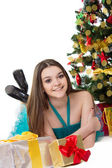 Brunette girl in fancy dress lying under Christmas tree — Stock Photo