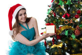 Teenage girl in Santa hat offering present under Christmas tree — Stok fotoğraf