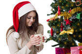 Teenage girl with coffee mug under Christmas tree — Stock Photo