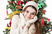Teenage girl in knitted mitten and hat under Christmas tree — Stock Photo