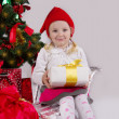 Girl in Santa hat with present on sledge — Stockfoto