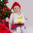 Girl in Santa hat with present on sledge — Stock fotografie