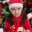 Girl in Santa hat holding Christmas gift — Stock Photo