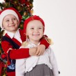 Sister and brother hugging under Christmas tree — Stock Photo