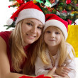 Mother and daughter under Christmas tree — Stock Photo