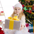 Blonde girl with present under Christmas tree — Lizenzfreies Foto
