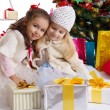 Lovely little girls with presents under Christmas tree — Stok fotoğraf