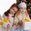 Little sisters with presents under Christmas tree — Stok fotoğraf