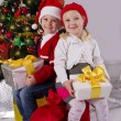 Little girl and boy sitting with gift under Christmas tree — Stock Photo