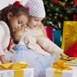 Lovely little girls with presents under Christmas tree — Stock Photo