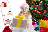 Blonde girl with present under Christmas tree — Stock Photo