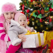 Sisters sitting with gifts under Christmas tree — Stock Photo #36343999